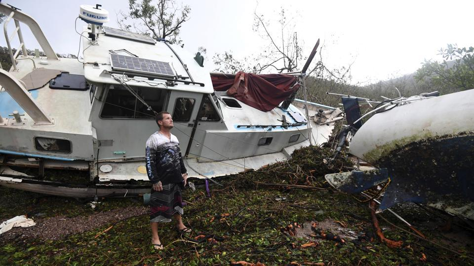 Bradley Mitchell inspects the damage to his uncle's boat after it smashed against the bank at Shute Harbour, Airlie Beach, Australia. Cyclone Debbie, which slammed into the coast of Queensland state on Tuesday with winds up to 260 kilometers (160 miles) an hour, weakened quickly as it moved inland and was downgraded to a tropical low.  (Dan Peled/AAP Image via AP)