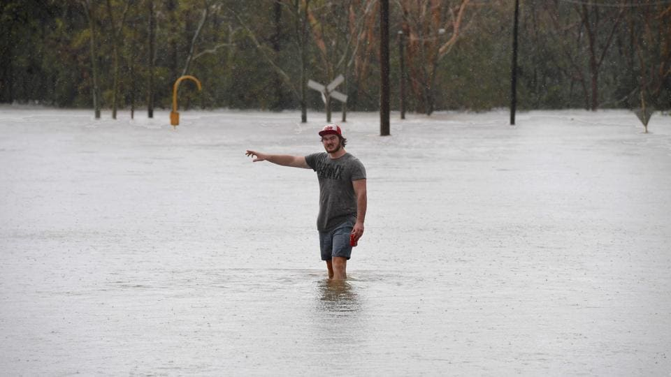 A local resident wades into flood waters blocking the road between the townships of Airlie Beach and Proserpine after Cyclone Debbie hit the area in northern Queensland. (AAP/Dan Peled/via REUTERS )