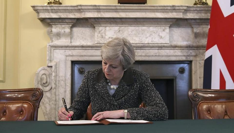 Britain's Prime Minister Theresa May signs the official letter to European Council President Donald Tusk, in 10 Downing Street, London, Tuesday March 28, 2017, invoking Article 50 of the bloc's key treaty, the formal start of exit negotiations.