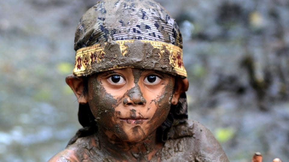 A Balinese boy puts mud on his body during a mud bath tradition known as Mebuug-buugan, in Kedonganan village, near Denpasar on Indonesia's resort island of Bali . (Sonny Tumbelaka / AFP)