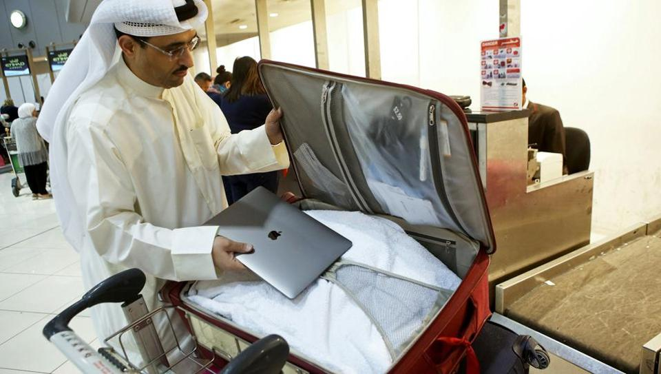 Kuwaiti social media activist Thamer al-Dakheel Bourashed puts his laptop inside his suitcase at Kuwait International Airport in Kuwait City before boarding a flight to the United States on March 23, 2017. Travellers across the Middle East have expressed frustration at a ban on large electronic devices for flights to the United States and Britain that has sparked confusion and speculation.