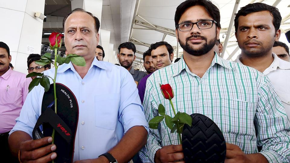 Protesters hold roses and slippers as they stage a demonstration against Shiv Sena MP Ravindra Gaikwad for his misbehaviour with an Air India staffer, at IGI Airport in New Delhi.