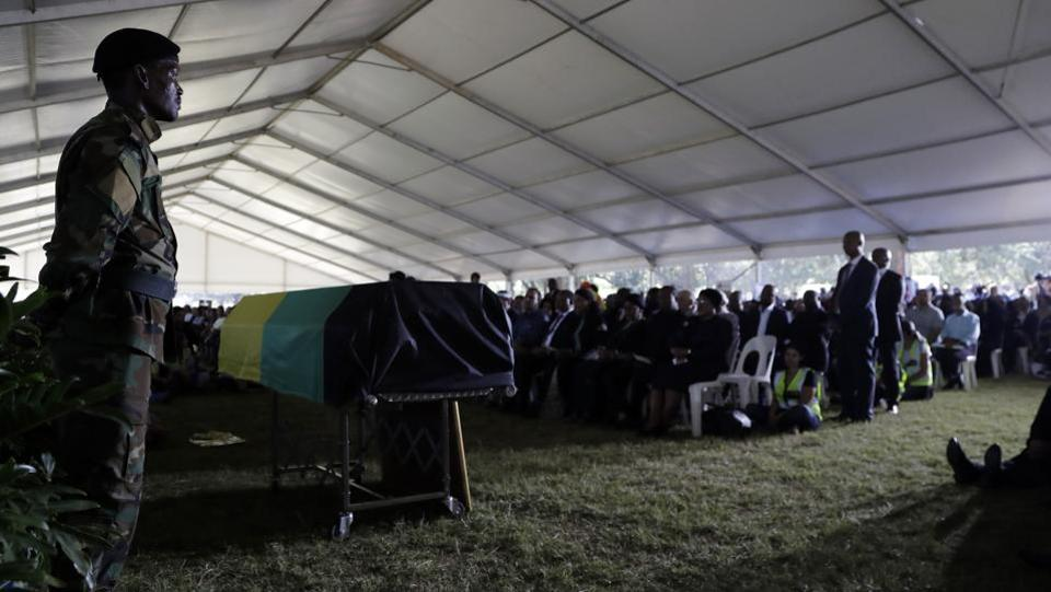A member of the African National Congress (ANC), stands next to a coffin during the funeral service for Ahmed Kathrada, at West Park Cemetery in Johannesburg. Kathrada died at a Johannesburg hospital after being admitted for surgery linked to blood clotting on the brain.  (Themba Hadebe/AP)