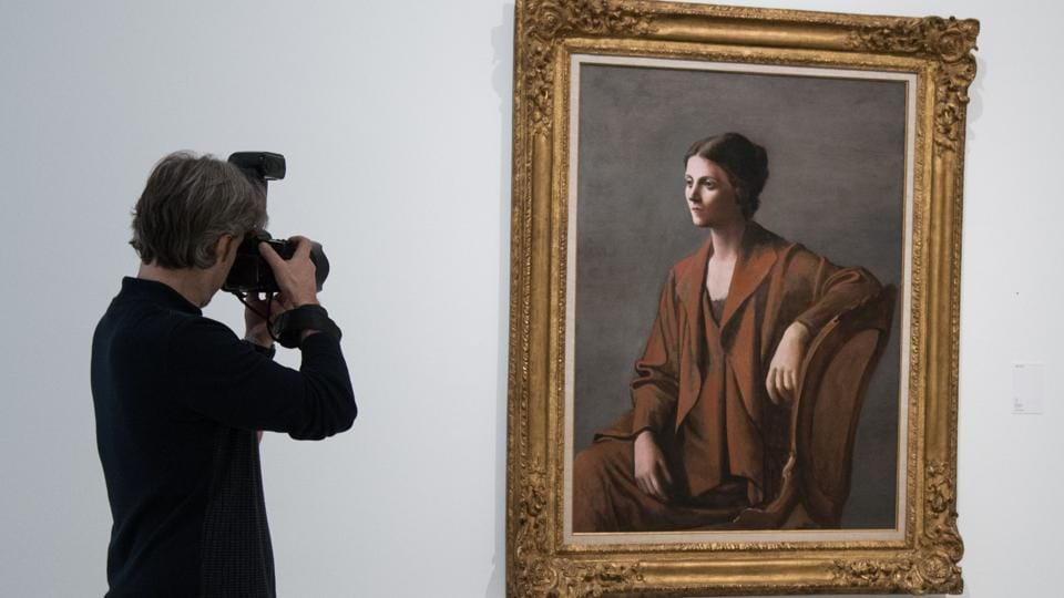 A man takes a picture of Spanish artist Pablo Picasso's painting 'Olga Picasso' displayed at the exhibition 'Picasso, Portraits' organised at the Picasso Museum in Barcelona on March 16.