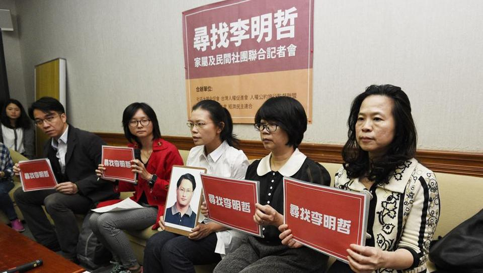 Lee Ching-yu (third from right) holds up a photo of her missing husband and Taiwanese pro-democracy activist Lee Ming-che in Taipei, Taiwan.