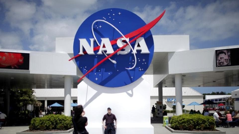 Tourists take pictures of a NASA sign at the Kennedy Space Center visitors complex in Cape Canaveral, Florida.