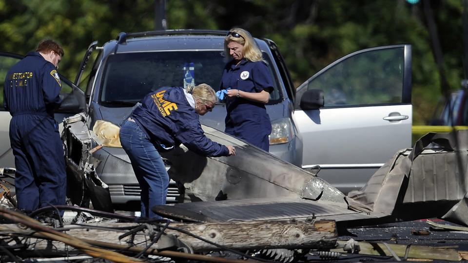 Investigators look at the remains of a small plane along Main Street in East Hartford, Connecticut.