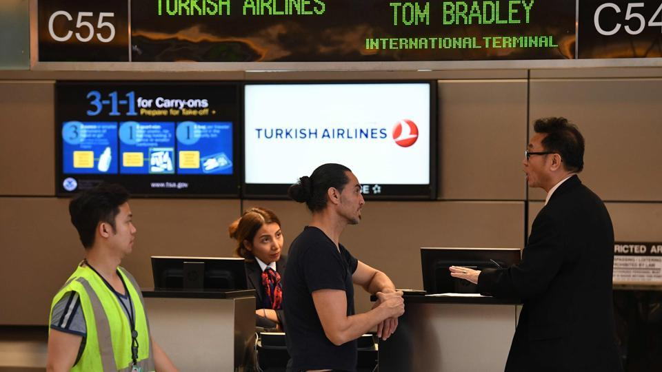 A passenger talks with a Turkish Airlines manager beside a check-in counter at Los Angeles International Airport in Los Angeles, California.