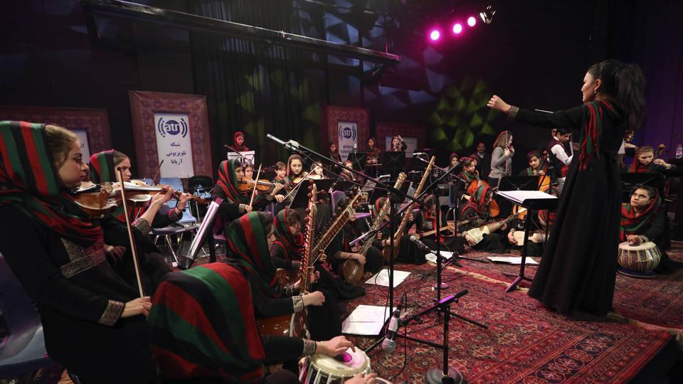 In this Wednesday, Feb. 15, 2017 photo, orchestra conductor Zarifa Adiba, 18, performs during a concert in Kabul. Afghanistan's first all-female symphony is trying to change attitudes in a deeply conservative country where many see music as immoral, especially for women.