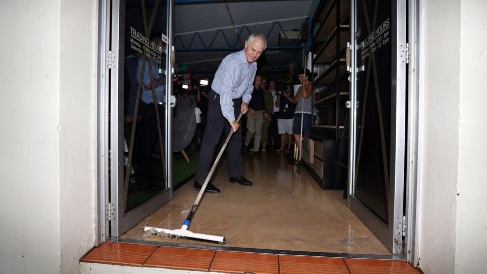 Australian Prime Minister Malcolm Turnbull wipes flood waters out of a building as he visits areas of Bowen in northern Queensland damaged by Cyclone Debbie on March 30.