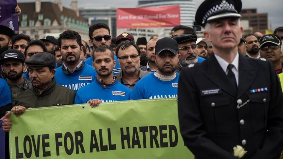 A police officer and British Muslims (blue T-shirt) take part in a vigil on Westminster Bridge. A 30-year-old man remains in custody and a 32-year-old woman has been bailed, having been arrested on suspicion of the same offence. (Oli Scraff/AFP)