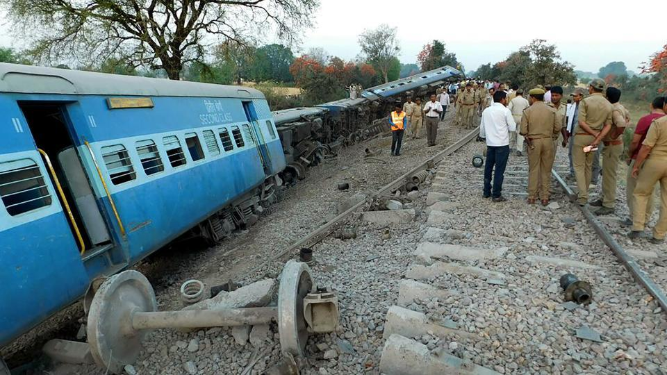 Rescue workers and officials are watched by bystanders as they inspect derailed coaches of the Mahakaushal Express at Mahoba some 140kms south-west of Kanpur on March 30.