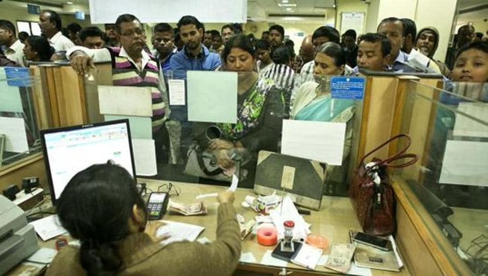 People deposit discontinued notes on the last day in a bank on December 30, 2016.