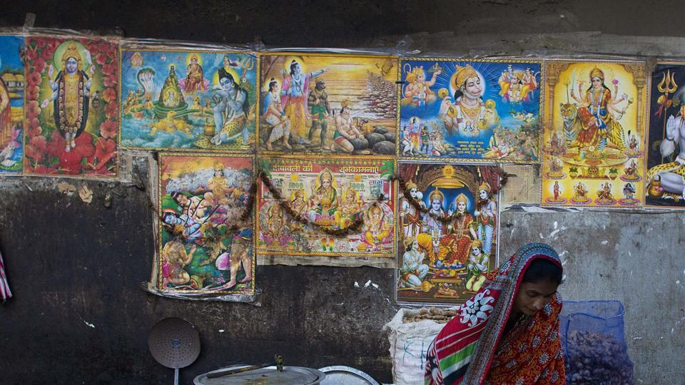 A pavement covered with posters of Hindu gods.