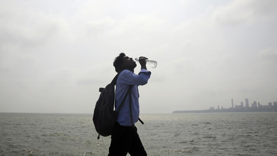 A man takes a drink as he walks by the Arabian sea in Mumbai on Thursday. Maharashtra is experiencing a heat wave condition with temperatures crossing 40 degrees Celsius in several areas.