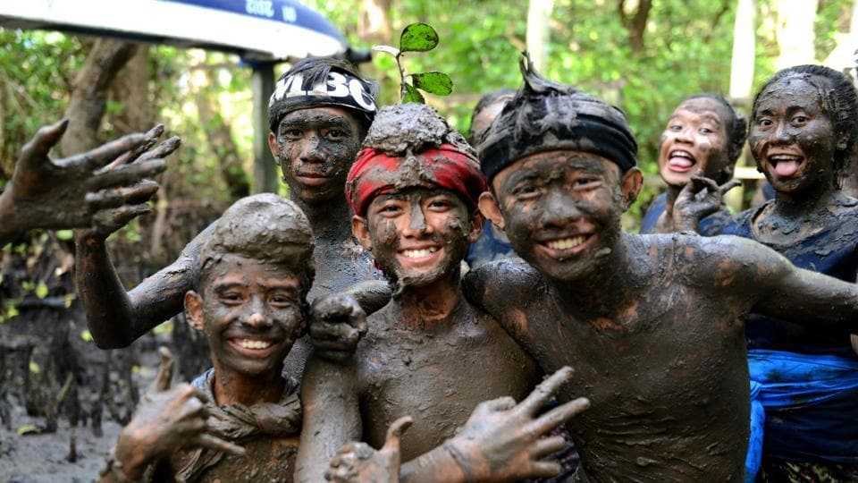 Children pose for a picture during the mud bath tradition known as Mebuug-buugan. (Sonny Tumbelaka / AFP)