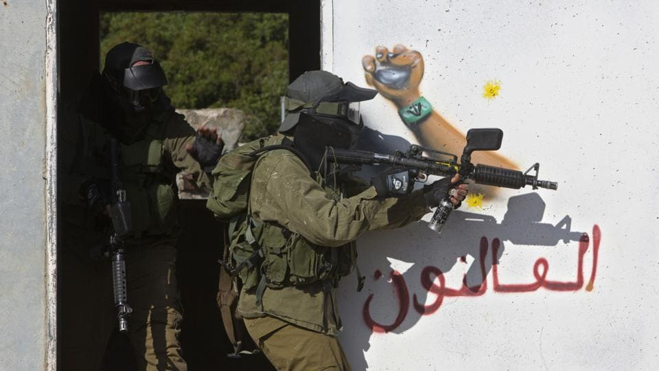 In this Wednesday, March 29, 2017 photo, Israeli soldiers train with paintball guns during a drill at an Army base near Elyakim, Israel.
