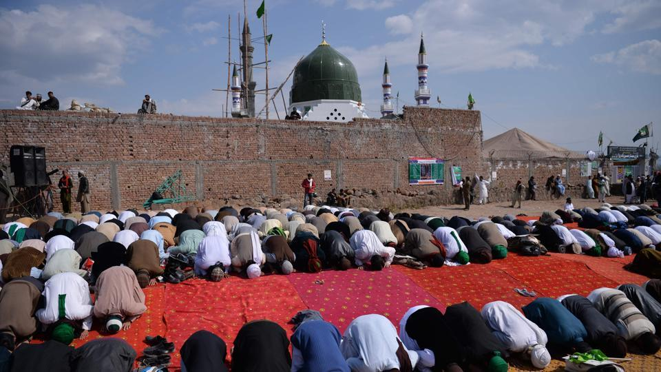 Pakistani Muslims offer noon prayers at the tomb of Mumtaz Qadri, who was hanged in February 2016 for the murder of a governor who criticized Pakistan's blasphemy law and defended a Christian woman, in Bara Kahu on the outskirts of Islamabad on March 1, 2017.