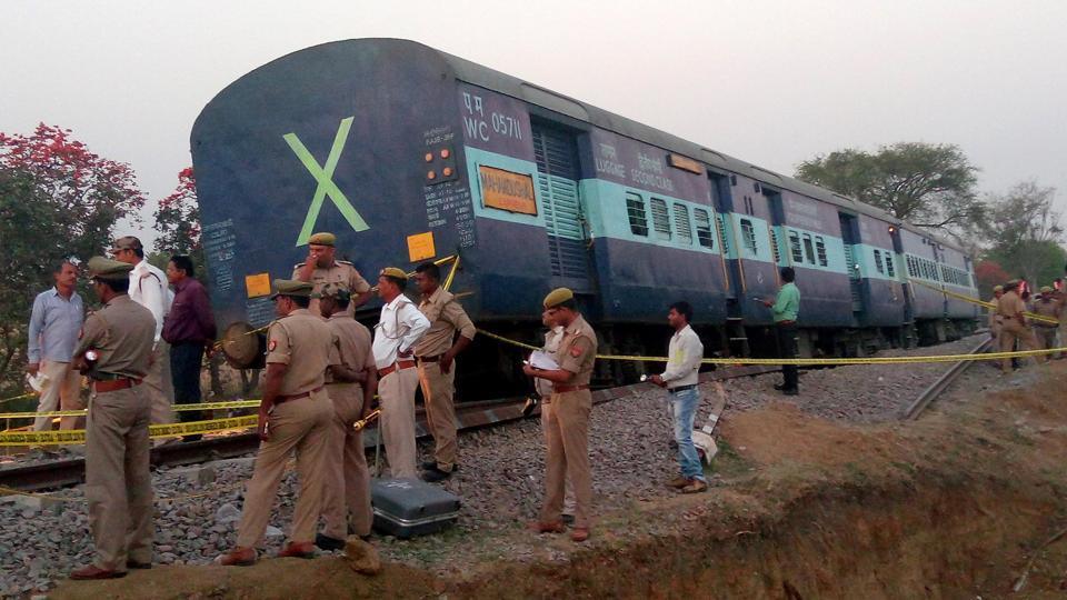 Police officials stand next to a derailed coach of a passenger train in Mahoba district in Uttar Pradesh, on March 30, 2017.