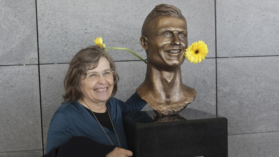 A woman poses next to the bust of Cristiano Ronaldo at the Madeira international airport. (AP)