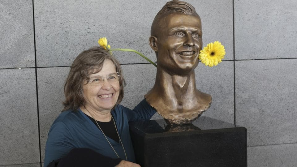 A woman poses next to the bust of Cristiano Ronaldo at the Madeira international airport outside Funchal, the capital of Madeira island, Portugal, on March 29, 2017. Madeira International Airport has been renamed after local football star Cristiano Ronaldo.