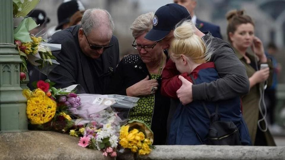People embrace after laying flowers during an event. Hundreds of people gathered at Westminster Bridge and outside the Houses of Parliament for a silent vigil to commemorate the four people who were murdered in last week's terror attack. (Hannah McKay/Reuters)