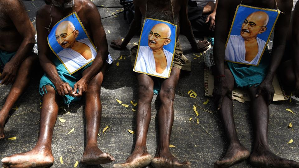Farmers from Tamil Nadu display posters of Mahatma Gandhi as they sit on protest. (Saumya Khandelwal/HT PHOTO)