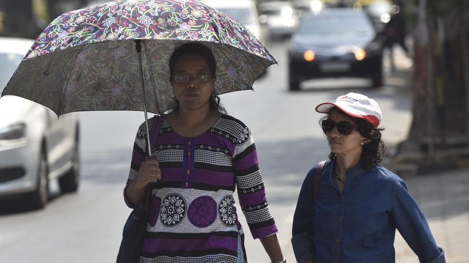 A woman walks with an umbrella as another wears a cap to protect themselves from heat, at Dadar in Mumbai.