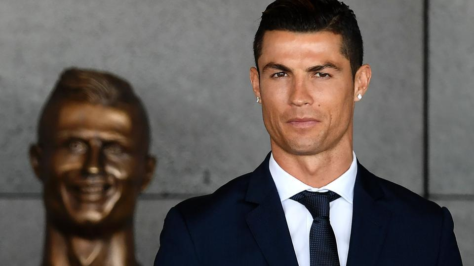 Cristiano Ronaldo stands past a bust uring a ceremony where Madeira's airport in Funchal was renamed after Ronaldo. (AFP)