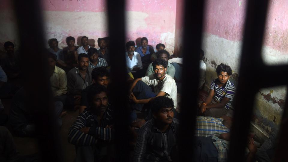 Indian fisherman sit in a police lockup in Karachi on March 26 after they were arrested by Pakistan coast guards.