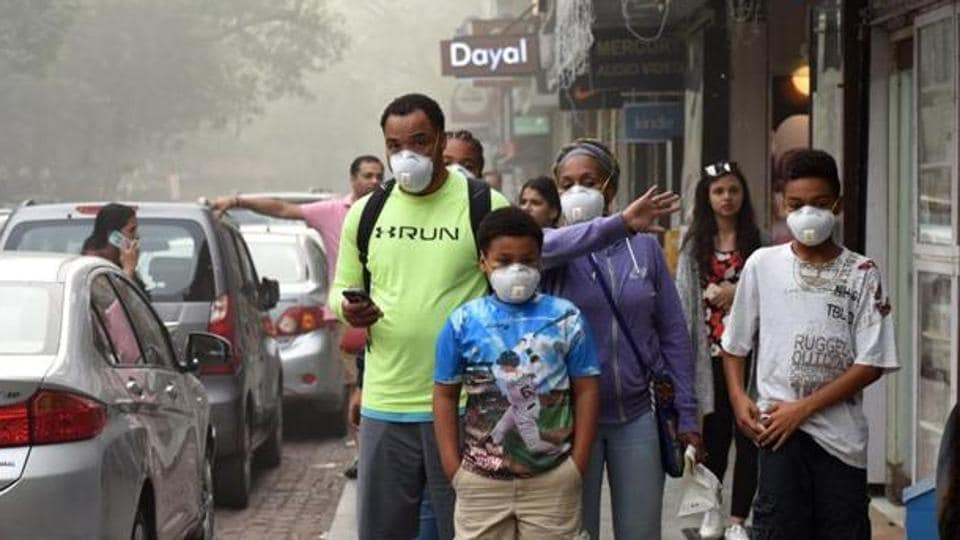 People walk wearing pollution masks at Khan Market in New Delhi.