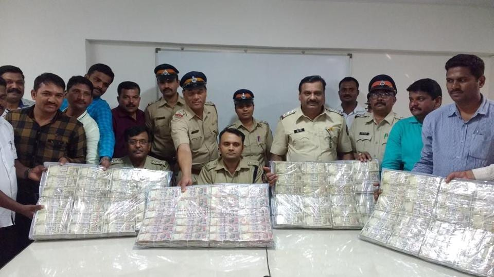 Police officers display the seized notes.