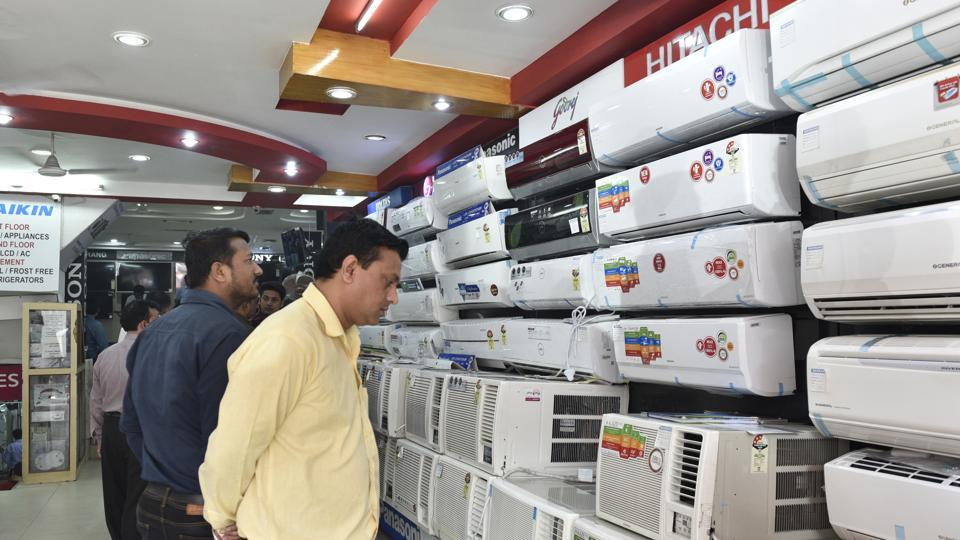 Customers check out air conditioners at a showroom in New Delhi on Friday.