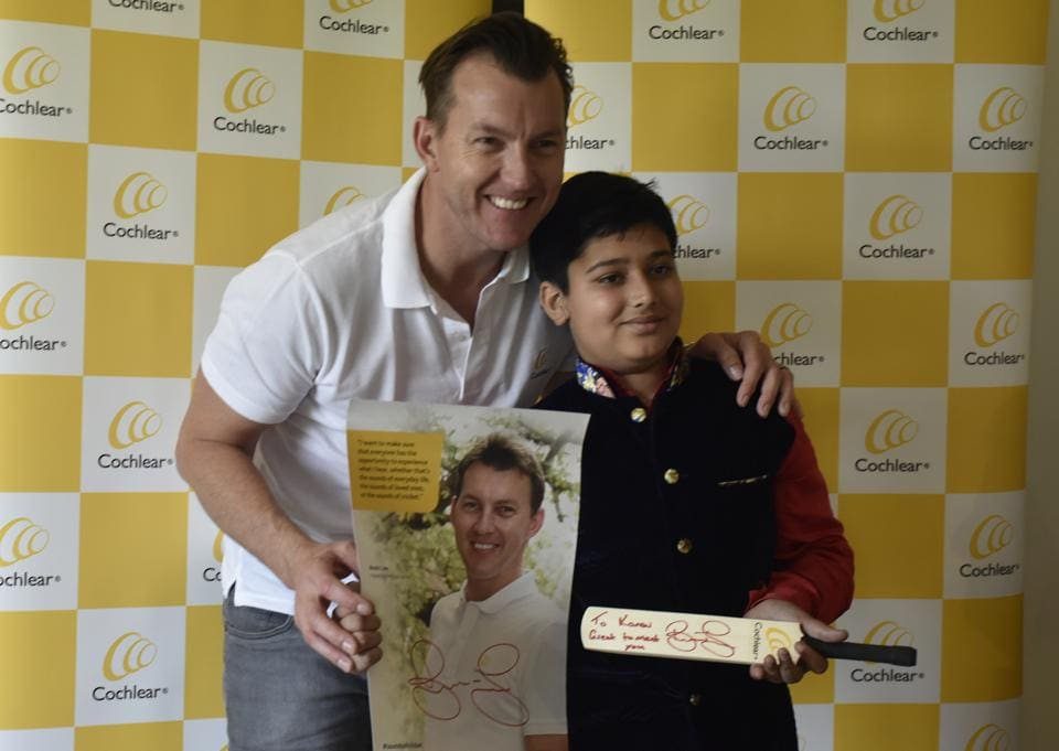 Brett Lee with Kanav Sharma, a young boy who was born wiht hearing impairment. A cochlear implant has partially restored his hearing ability. Lee works to spread awareness about hearing problems.