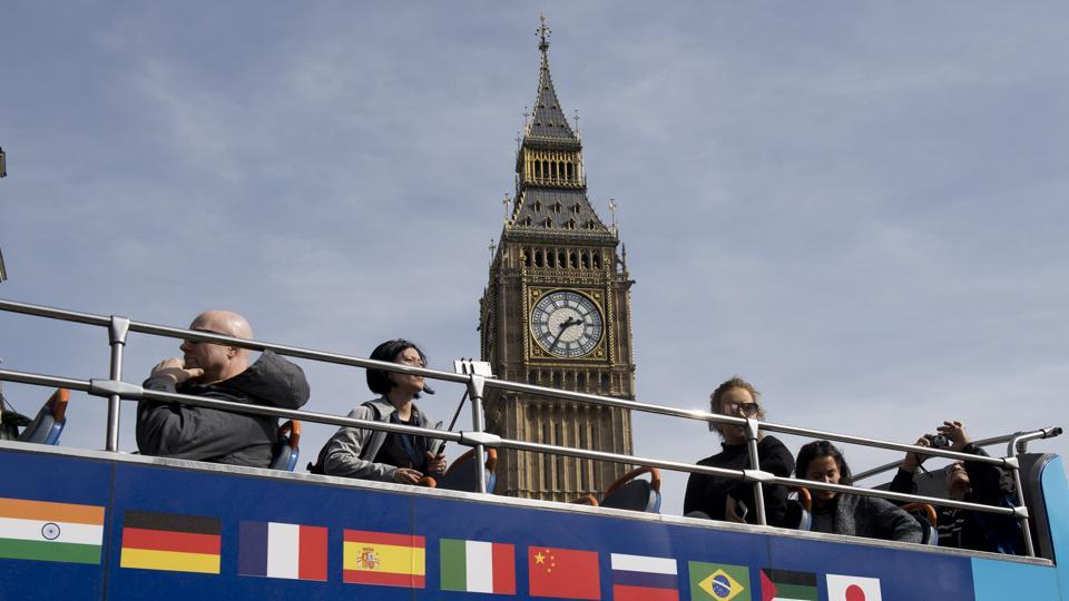 A tourist bus passes Big Ben at the Houses of Parliament in London on March 30, 2017. Britain launched the historic process of leaving the EU on Wednesday, saying there was
