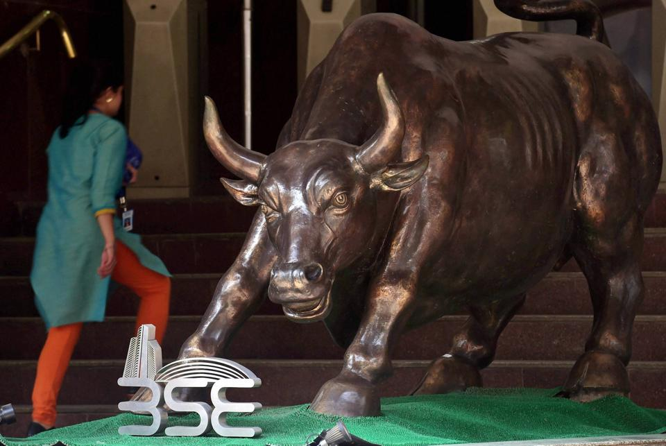 A woman walks past a bronze replica of a bull at the Bombay Stock Exchange as Sensex closed 486 points up, in Mumbai.