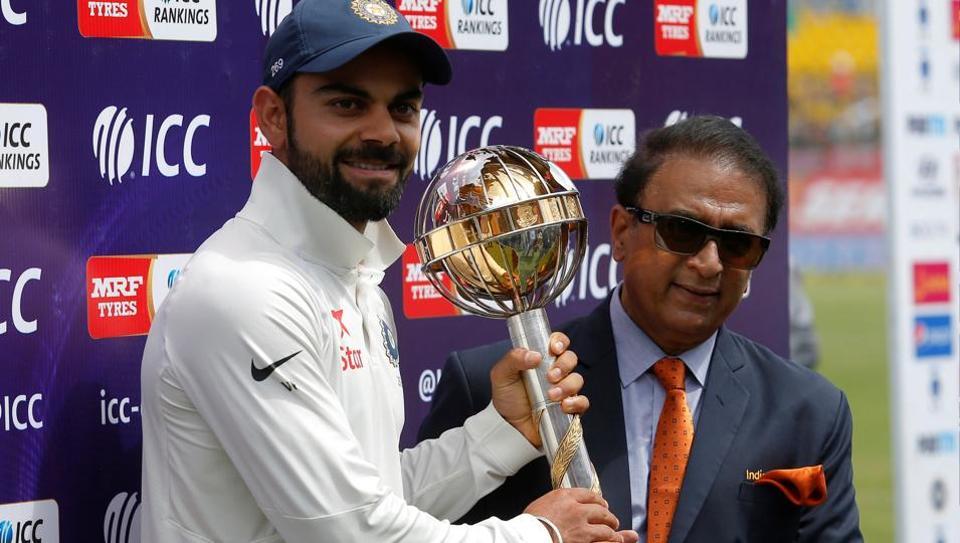 India skipper Virat Kohli receives the ICC Test Mace from cricket great Sunil Gavaskar (R) after India won the Test series against Australia.