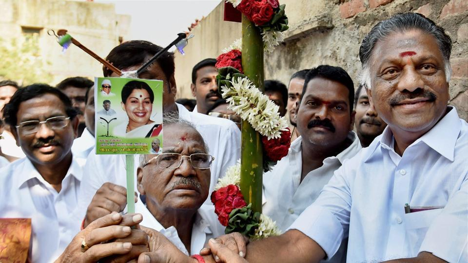 AIADMK Puratchi Thalaivi Amma leader O Panneerselvam presents the party sympbol (electric pole) to RK Nagar bypoll candidate E Madhusudhanan in Chennai.