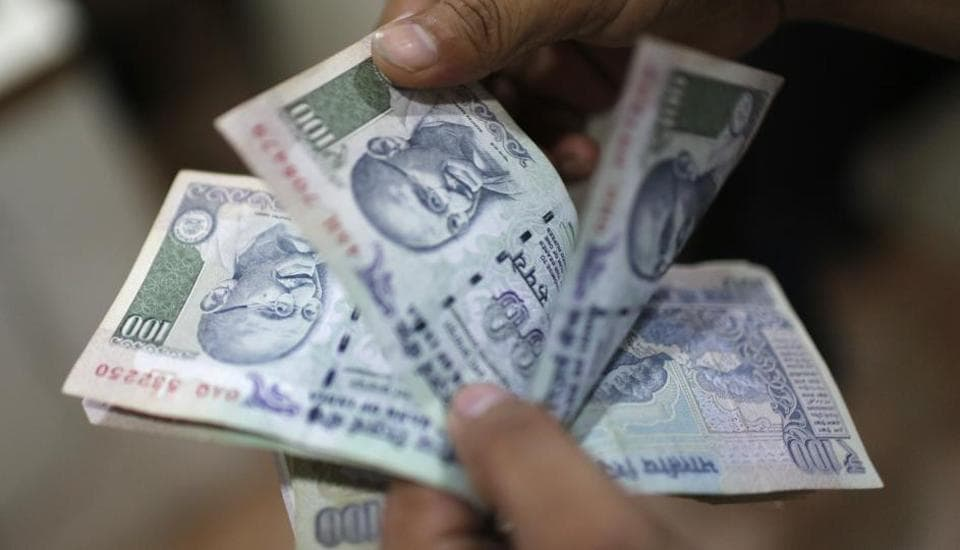 An man counts money inside a private money exchange office in New Delhi.