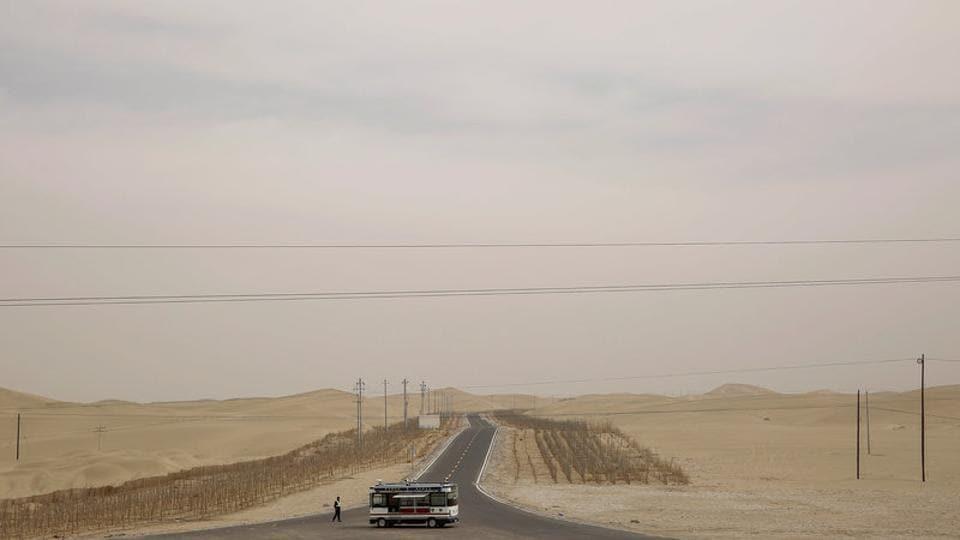 Police keep watch on a road running through the Taklamakan Desert outside Hotan, Xinjiang Uyghur Autonomous Region, China. (Thomas Peter/REUTERS)