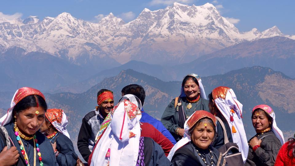 Women from the Bhutia community in traditional attire from the surrounding Chamoli district visit the Kartik Swami Temple on a festive occasion, seen here in the backdrop of higher Himalayan ranges including Chaukhamba, right, and the Kedarnath ranges, left. (Gurinder Osan/HT Photo)