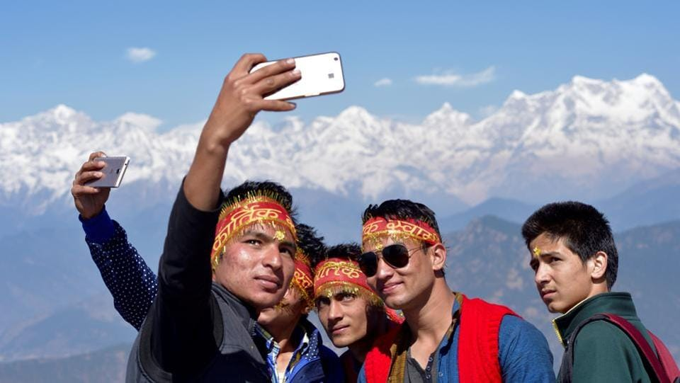 Young locals from Garhwal engage in shooting selfies at the temple. (Gurinder Osan/HT Photo)