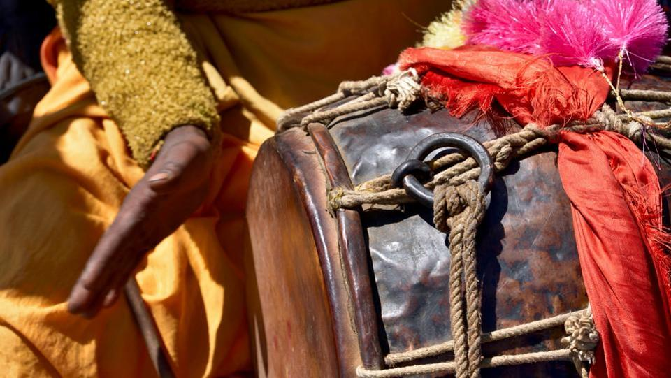 A percussionist from a nearby village, plays his drum, the sound of which is carried to all neighbouring villages to announce continuing festivities on an auspicious day at the Kartik Swami Temple. (Gurinder Osan/HT Photo)