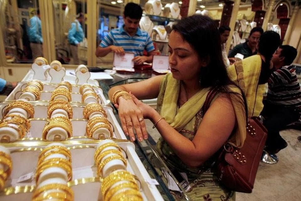 A woman tries on a gold bracelet at a jewellery showroom.