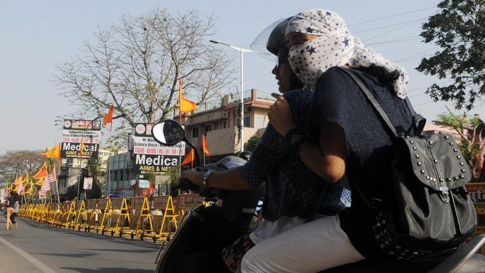 Girls with faces  covered riding a deserted street  in Ranchi as  temperature  soared to an all time high  on Thursday
