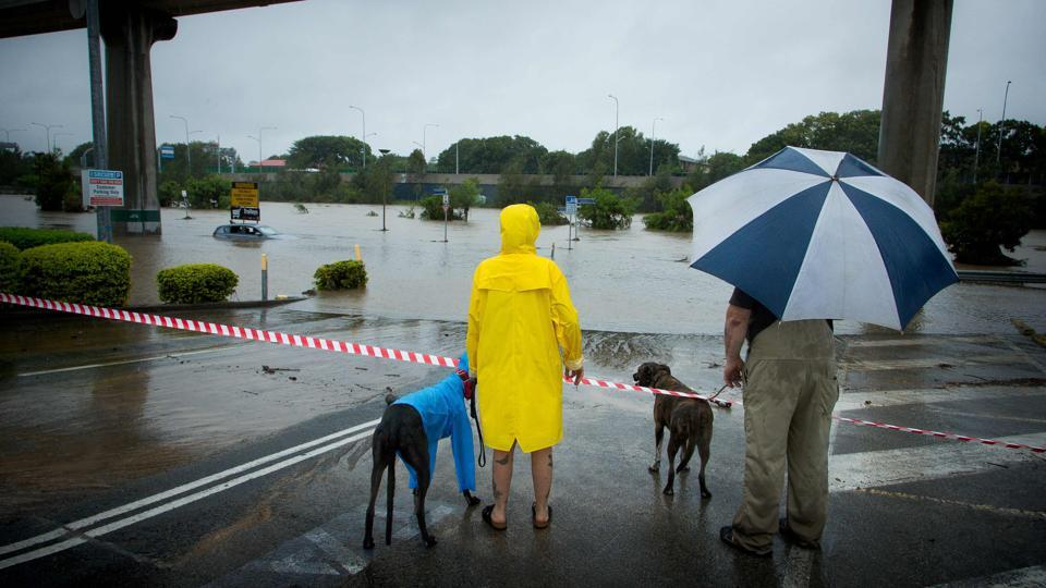 Onlookers look at submerged cars in a flooded car-park in Toombul, in Queensland. Torrential rain hampered relief efforts after powerful cyclone Debbie wreaked havoc in northeast Australia, with floods sparking emergency rescues as fed-up tourists began evacuating from resort islands.  (Patrick Hamilton/AFP)