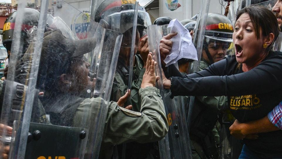 Venezuelan opposition deputy Amelia Belisario (2nd-R) scuffles with National Guard personnel in riot gear during a protest in front of the Supreme Court in Caracas on March 30.
