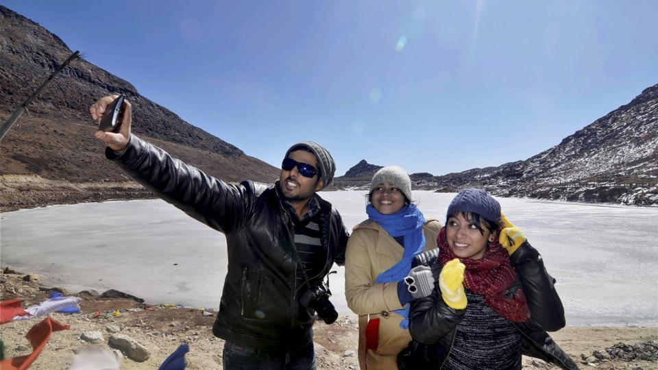 Tourists take a selfie in front of a frozen lake in Tawang, a strategically important point along India-China border in Arunachal Pradesh.