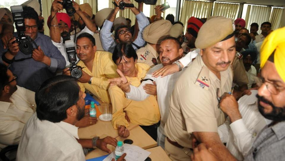 Police officials trying to control Congress councillors at municipal corporation in Jalandhar on Friday.