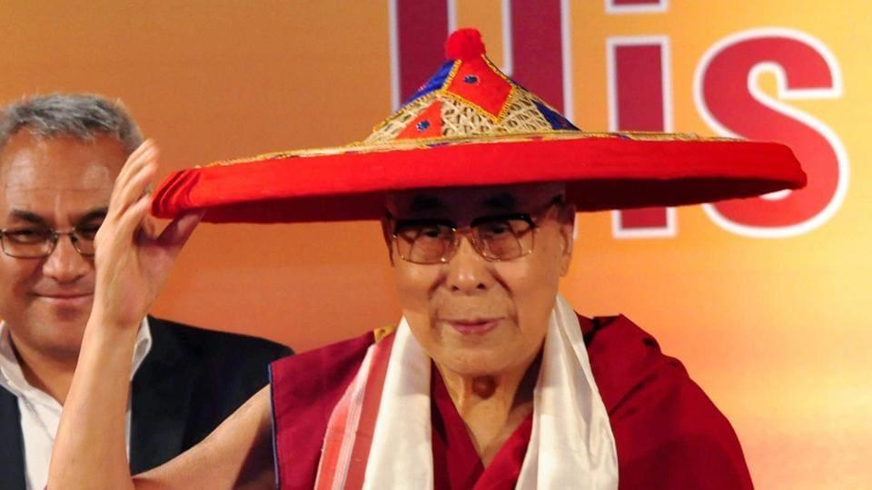 Tibetan spiritual leader the Dalai Lama being feliciated with an Assamese Japi at an event in Guwahati on Saturday.